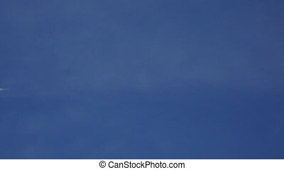 Flying commercial airplane leaving contrain in blue sky. 4K...