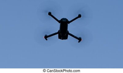Flying copter in the blue sky. Bottom view - Fying black...