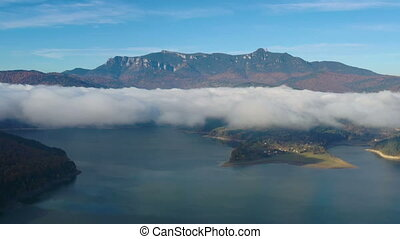 Flying drone in autumn morning, mist over mountain lake. - ...