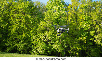 Flying drone is filming in the forest background