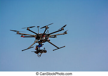 flying drone with a camera on blue sky background