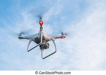 Flying drone with blue sky background