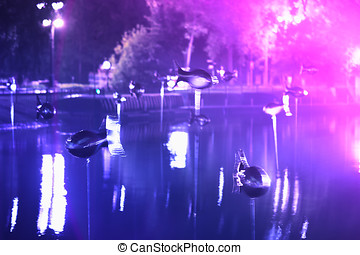 Flying fishes in Moscow park at light show background hd