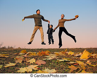 flying happy family with autumn leaves. color sunset sky
