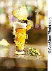 Flying heart splash of light beer above glass of fresh beverage.