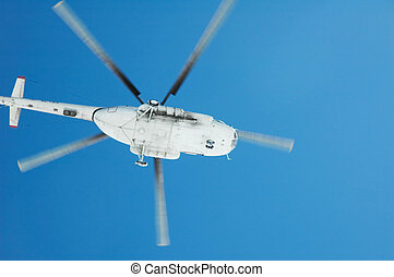 Flying helicopter against blue sky on bright day