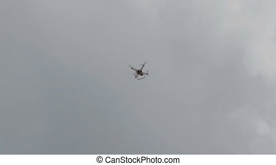Flying helicopter dron on a background of white clouds.