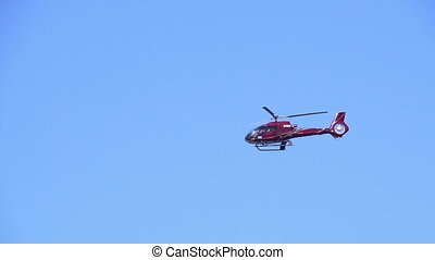Flying Helicopter - In the clear sky flies a small modern...