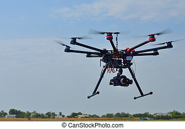 flying helicopter with camera over meadow