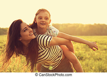 Flying kid girl laughing on the happy enjoying mother back on sunset bright summer background. Closeup toned color bright portrait.