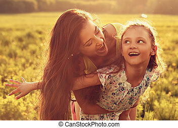 Flying kid girl laughing with happy enjoying mother on sunset bright summer background. Closeup toned color portrait.