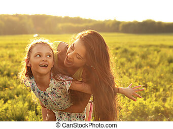 Flying kid girl laughing with happy enjoying mother on sunset bright summer background. Closeup portrait.