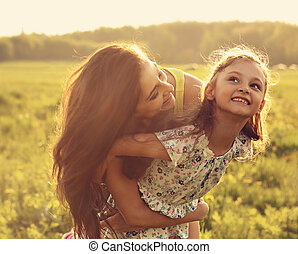 Flying kid girl laughing with happy enjoying mother on sunset bright summer background. Closeup toned portrait.