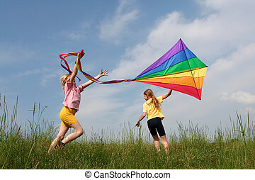 Flying kite - Children flying rainbow kite in the meadow on ...