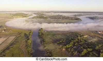 Flying low over the calm river. Dense fog over the water.