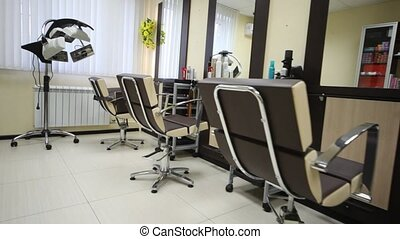 Flying motion of camera in salon hairdressing salon along armchairs to window