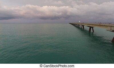Flying near pier - Aerial view of sea and old pier
