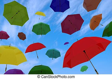flying of multicoloured umbrellas on a background blue sky with clouds
