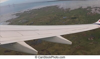 COPENHAGEN, DENMARK - MAY 11, 2018: View from plane window on a flight taking off from Copenhagen Airport, the Oresund bridge visible on the horizon