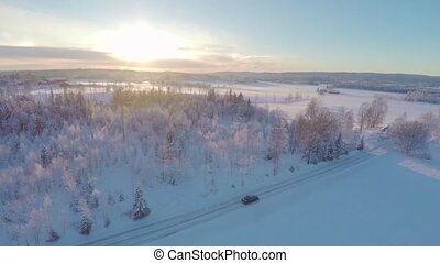 Flying over a car driving in winter landscape at sunset