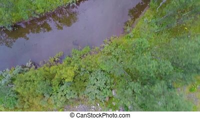 Flying over a creek and trees between high mountains -...