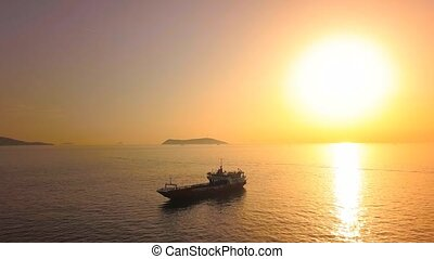 Flying over a landing boat against the sun. Silhouette of the bulk carrier ship sailing into Marmara Sea at sunset. View from aerial camera