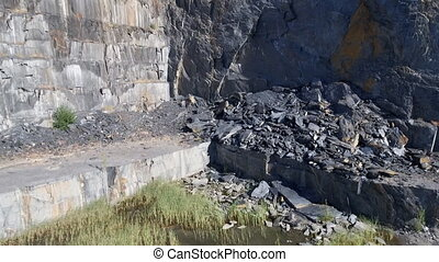 Flying over abandoned slate mine wall - Ascending camera...