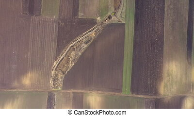 Flying over agricultural field with chemical fertilizer in...