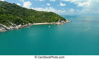 flying over amazing white sand beach and tropical lagoon with yacht