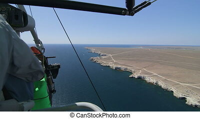 Flying over Black sea coast on motorized hang glider,...