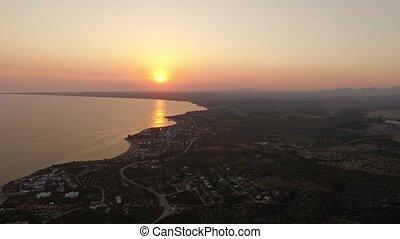 Flying over coastal Trikorfo Beach at sunset, Greece -...