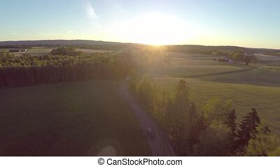 Flying over crops and cars on country road in sunset -...