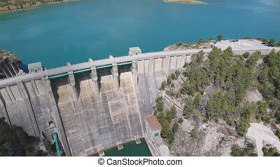 Flying over dam, descending - Descending over dam with green...