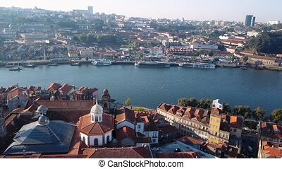 Flying over Douro river and Ribeira, Porto, Portugal. Aerial view the roofs of old city center.