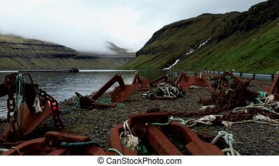 Flying over old rusty anchors in the shore of fjord