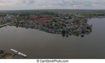 Flying over riverside township in Netherlands