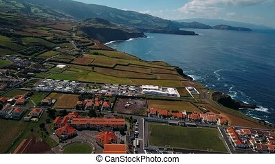 Flying over San Miguel island coast, Maia city, Azores...