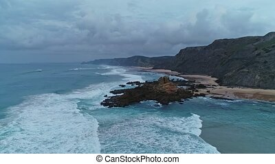 Flying over sandy beach and rocks in Portugal