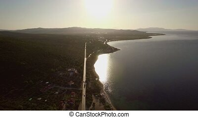 Flying over sea and coast with road along waterfront....