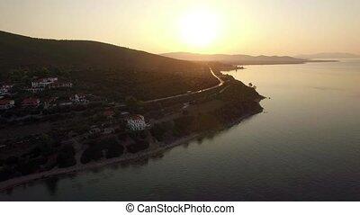 Flying over sea and Trikorfo Beach coastline at sunset,...