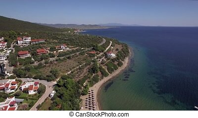 Flying over sea, cottages and resort on the coast. Trikorfo...