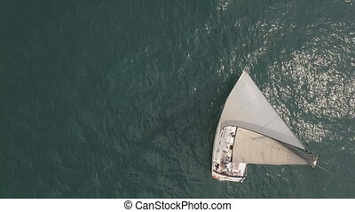 Flying over sea with sailboat - Aerial view of calm sea with...