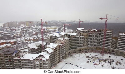 Flying over suburbs of winter city and construction site of...