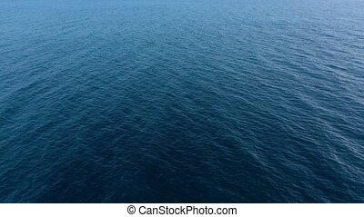Flying over the blue surface of the sea or ocean - Aerial...