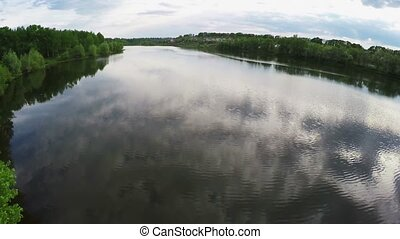 Flying over the calm lake and trees