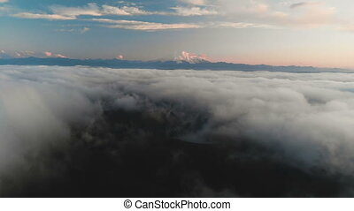 Flying over the clouds at dusk or at dawn. Flying above the...