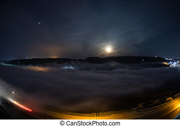 Flying over the deep night clouds with moon light. Moon rising over clouds with night city lights. Natural long shutter photo. Selective focus