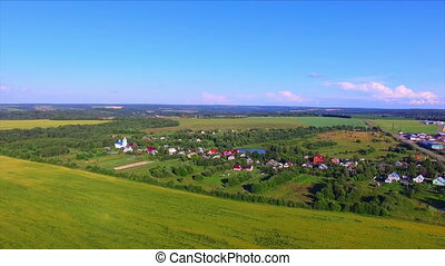 Flying over the farmland with cultivated fields and village...