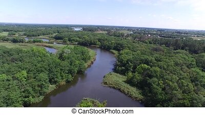 Flying over the forest and the river with lots influx,...