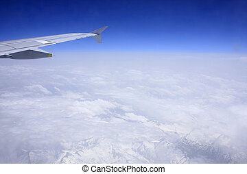Flying over the mountains; blue sky with Alps underneath the clouds;